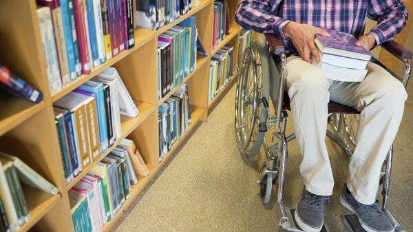 Мужчина на инвалидной коляске в библиотеке