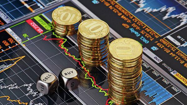 Стопки десятирублевых монет на экране с биржевыми графиками