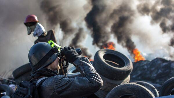 Сторонник радикальной оппозиции наблюдает в бинокль за перемещениями милиционеров на баррикаде на улице Институтской. Архивное фото