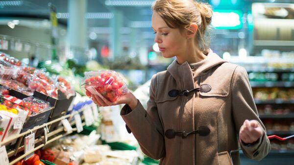 Женщина выбирает продукты в магазине. Архивное фото