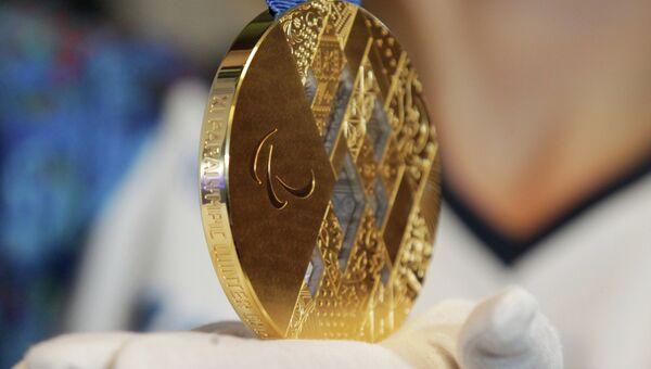 Девушка демонстрирует золотую медаль Паралимпиады-2014