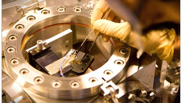 Ученые устанавливают мембрану в вакуумную камеру сверхчувствительного лазерного детектора радиоволн