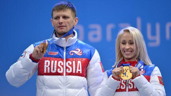 Ведущий Алексей Иванов и Михалина Лысова (Россия), завоевавшие золотые медали в спринтерской гонке в классе B 1-3 (слабовидящие) среди женщин в соревнованиях по лыжным гонкам