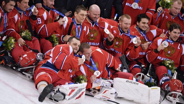 Игроки сборной России, завоевавшие серебряные медали на соревнованиях по следж-хоккею на XI зимних Паралимпийских играх в Сочи, во время медальной церемонии