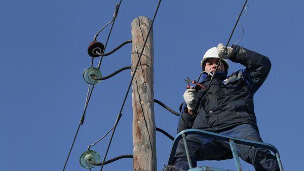 Электрик на опоре линии электропередачи