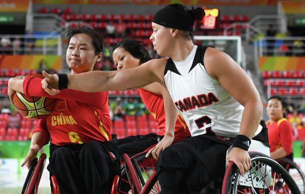 Игрок сборной КНР Юнь Лун и игрок сборной Канады Синди Оуллет (справа)