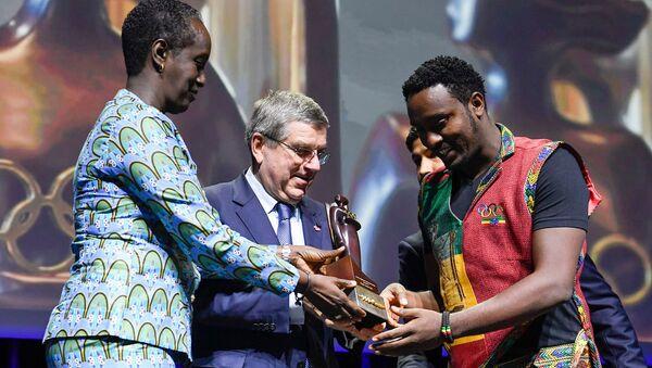 Эфиопский спортивный журналист Дагим Зинабу Текле (справа) получает награду МОК Женщины и спорт
