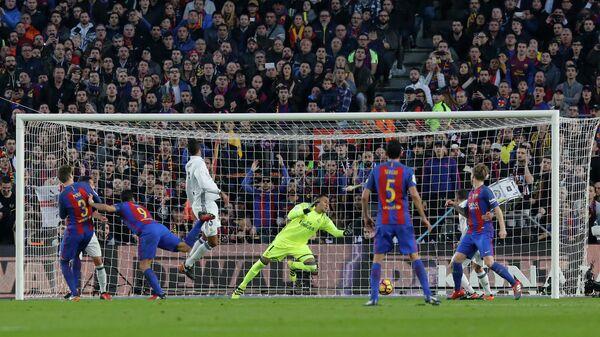 Форвард Барселоны Луис Суарес (третий слева) забивает мяч в ворота голкипера мадридского Реала Кейлора Наваса
