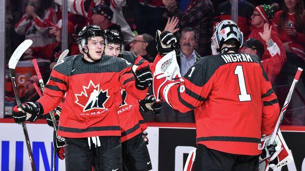 Хоккеисты молодежной сборной Канады Митчелл Стивенс (слева) и Коннор Ингрэм радуются заброшенной шайбе