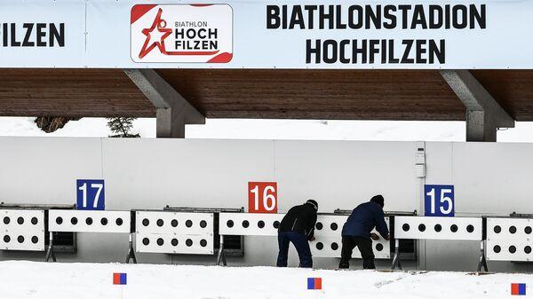Служащие меняют мишени на стрельбище во время тренировки перед началом чемпионата мира по биатлону в Австрии