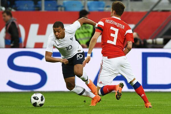 Нападающий сборной Франции по футболу Килиан Мбаппе и защитник сборной России Роман Нойштедтер (слева направо)