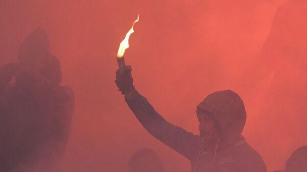 Футбольный фанат с зажженным фаером
