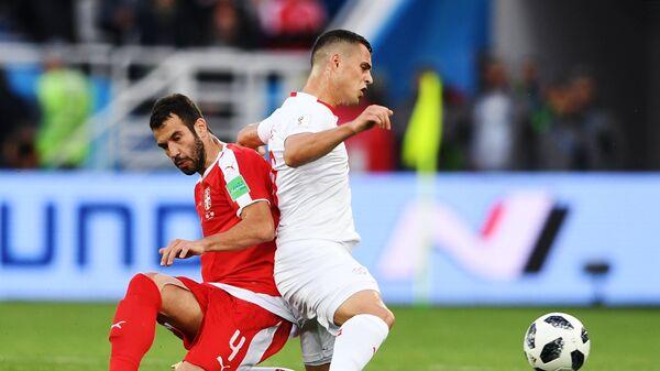 Полузащитник сборной Сербии Лука Миливоевич и швейцарский полузащитник Гранит Джака (слева направо)