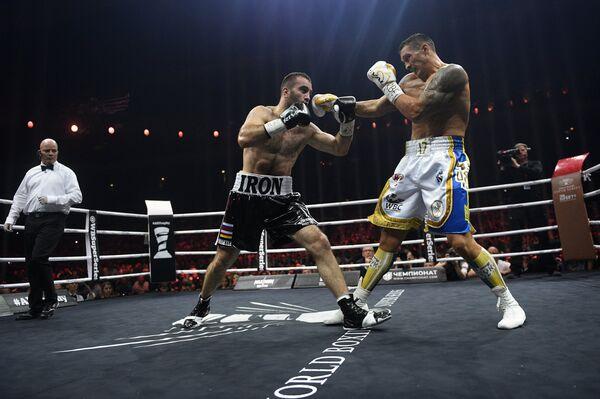 Бой между Муратом Гассиевым (слева) и Александром Усиком (справа)