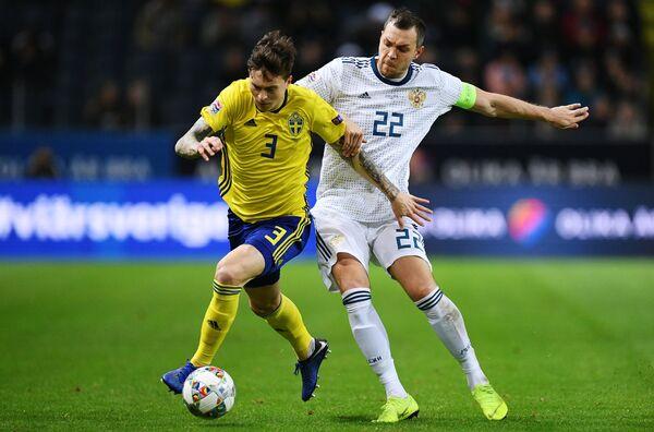 Защитник сборной Швеции Виктор Линделёф и нападающий сборной России Артём Дзюба (справа)