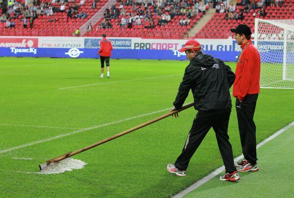 Сотрудники стадиона Локомотив убирают воду с футбольного поля