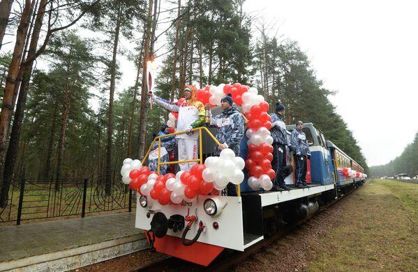 Факелоносец едет на поезде по детской железной дороге во время Эстафеты олимпийского огня в Ярославле