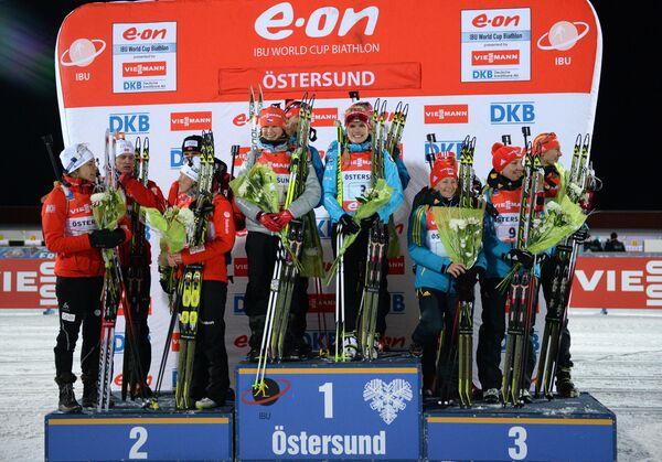 Призеры смешанной эстафеты на первом этапе Кубка мира по биатлону 2013/14 в шведском Эстерсунде во время церемонии награждения
