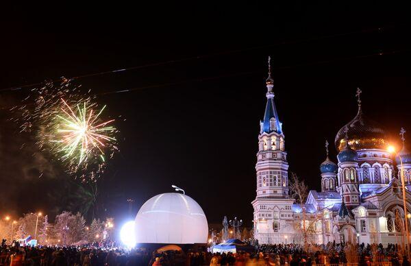 Зрители смотрят салют на торжественной церемонии зажжения чаши олимпийского огня в Омске