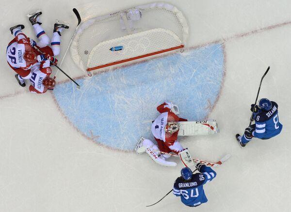 Вратарь российской сборной Семен Варламов пропускает шайбу от форварда финской сборной Теему Селянне (крайний справа)