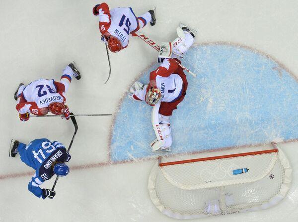 Российский голкипер Семен Варламов пропускает шайбу от форварда финской сборной Микаэля Гранлунда (крайний слева)
