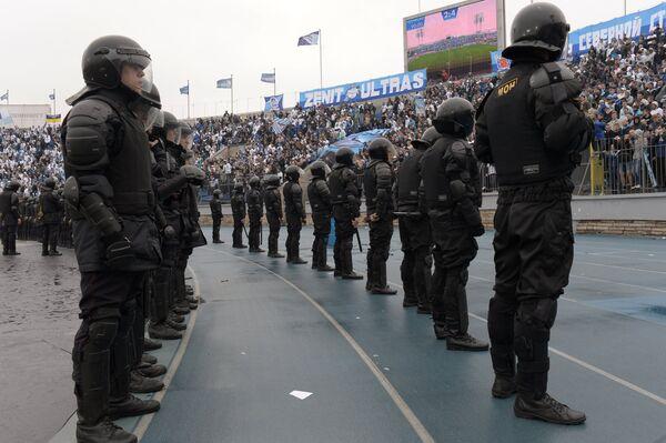 Сотрудники правоохранительных органов стоят в оцеплении у трибун на стадионе Петровский во время матча 29-го тура чемпионата России по футболу Зенит - Динамо