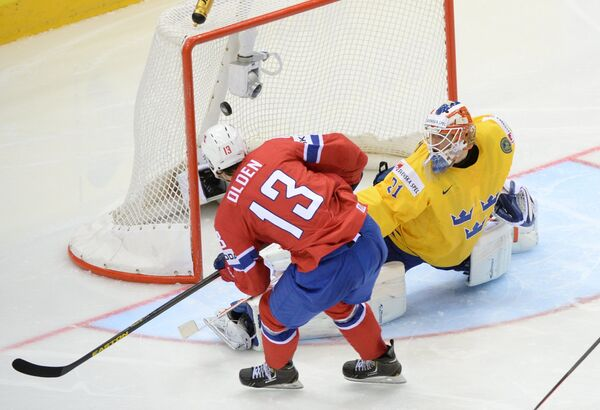 Форвард сборной Норвегии Сондре Олден (справа) забивает шайбу в ворота шведского голкипера Андерса Нильссона