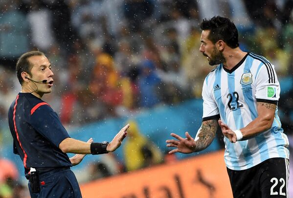Главный судья Джюнейт Чакыр и форвард сборной Аргентины Эсекьель Лавесси (справа).