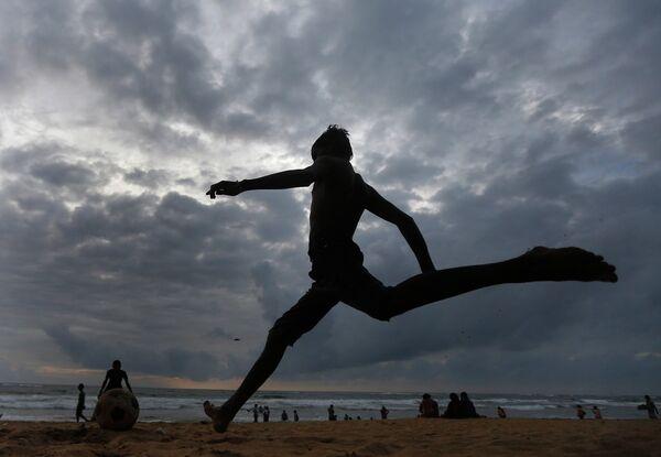 Мальчик наносит удар по мячу на пляже в Коломбо, Шри-Ланка