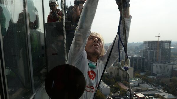 Французский скалолаз Ален Робер по прозвищу Человек-паук во время подъема на небоскреб Высоцкий в Екатеринбурге