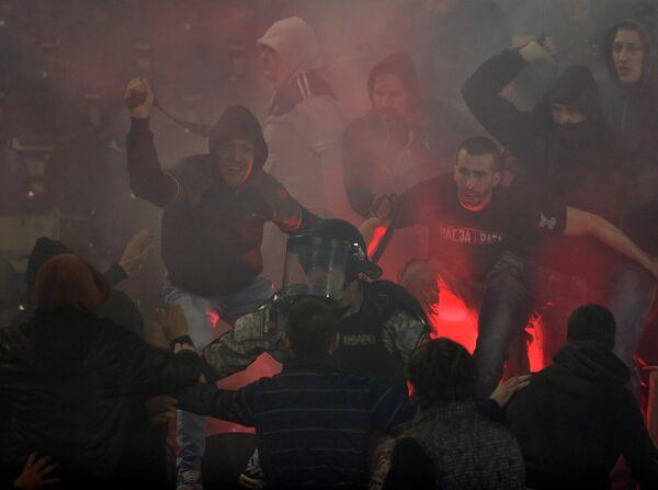 Полицейский между фанатами Партизана и Црвены Звезды