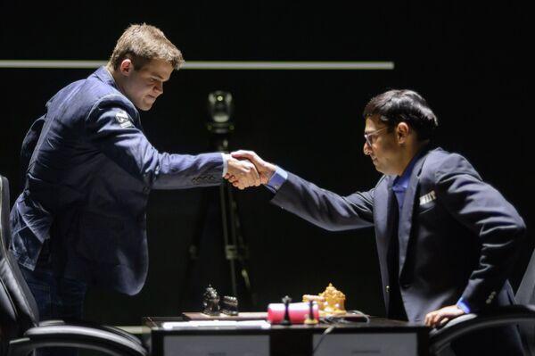 Обладатель титула Магнус Карлсен (слева) и претендент, индийский гроссмейстер Вишванатан Ананд перед началом первой партии матча за звание чемпиона мира по шахматам в Сочи