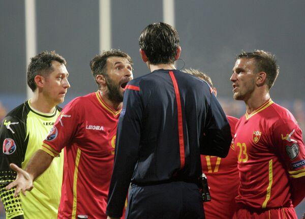 Футболисты сборной Черногории Марко Симич и Мирко Вучинич (справа налево) и главный арбитр матча Дениз Айтекин