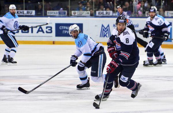 Форвард ХК Сибирь Калле Риддервалль и нападающий ХК Металлург Войтек Вольский (слева направо на первом плане)