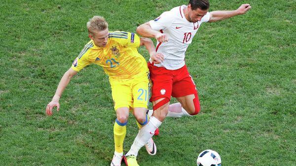 Хавбек сборной Украины Александр Зинченко и полузащитник сборной Польши Гжегож Крыховяк (слева направо)