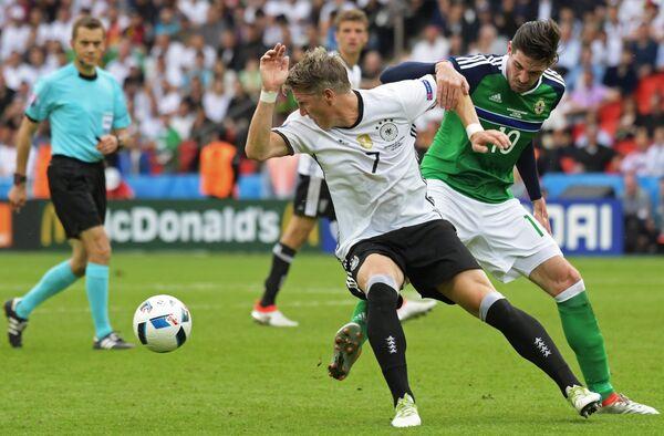 Нападающий сборной Северной Ирландии Кайл Лафферти и полузащитник сборной Германии Бастиан Швайнштайгер (справа налево)